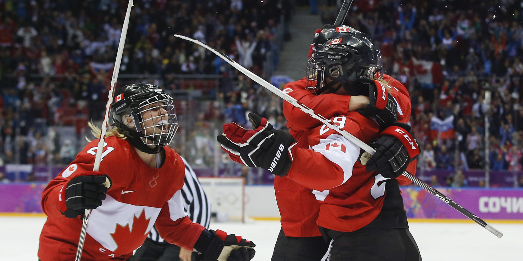 Haley Irwin of Canada (21) celebrates with teammates Marie-Philip Poulin (29) and Meghan Agosta-Marciano (2) after Poulin scored the tying goal against the USA during the third period of the women's gold medal ice hockey game at the 2014 Winter Olympics, Thursday, Feb. 20, 2014, in Sochi, Russia. (AP Photo/Matt Slocum)