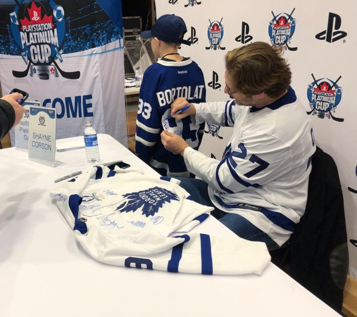 Former Toronto Maple Leaf Shayne Corson signs autographs for players.